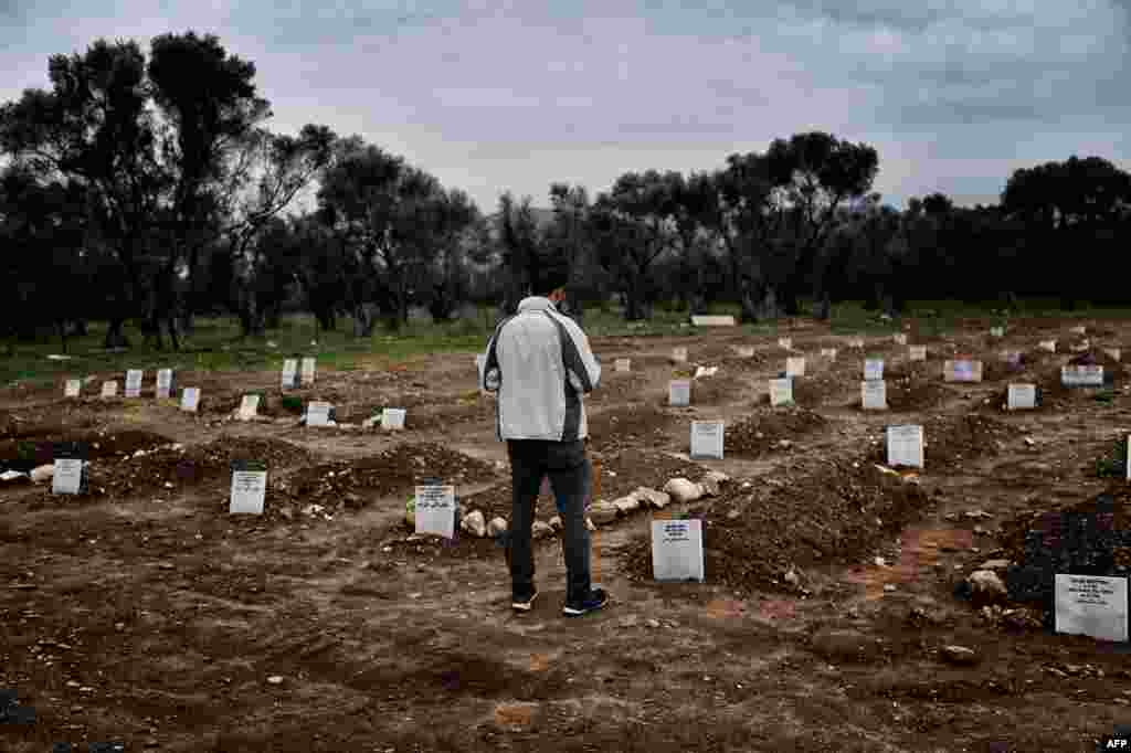 A man looks at the graves in Mytilene, Greece, at a graveyard for refugees and migrants who drowned in their attempt to cross the Aegean sea from Turkey to the island of Lesbos.