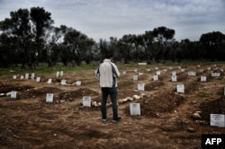 A man looks at a graveyard in Mytilene, Greece, Feb. 17, 2016, for refugees and migrants who drowned in their attempt to cross the Aegean sea from Turkey to the island of Lesbos.