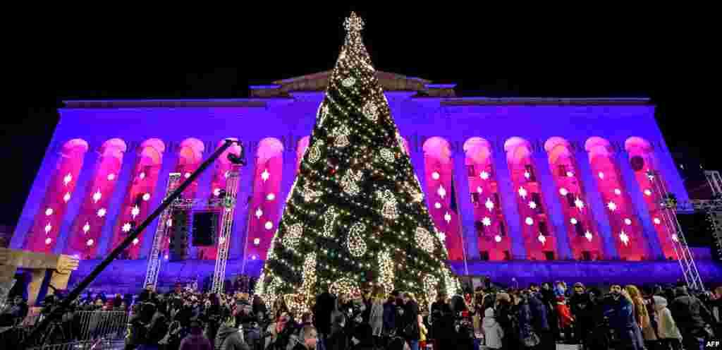 قدم زدن مردم مقابل درخت کریسمس تزئین شده در تفلیس گرجستان