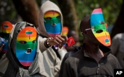 FILE - Kenya gay and lesbian activists conceal their identity behind masks to protest a wave of laws against homosexuality in African countries, Feb. 10, 2014.