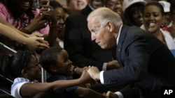 Vice President Joe Biden greets Lawrence Smith, 8, and Madison King, 9, both of Van Buren Township, Michigan, during a campaign stop at Renaissance High School in Detroit, Michigan, August 22, 2012.