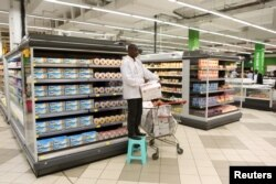An employee works at the cheese section of Hyper Hayat supermarket at the newly expanded Cap Sud shopping mall in Abidjan, Ivory Coast, Sept. 14, 2015.