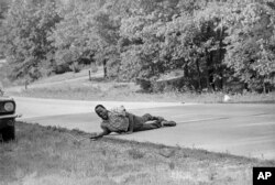 This June 6, 1966 file photo, shows civil rights activist James Meredith grimacing in pain as he pulls himself across Highway 51 after being shot in Hernando, Miss., during his March Against Fear. (AP Photo/Jack Thornell, File)