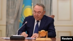 Kazakh President Nursultan Nazarbayev writes during a televised address to announce his resignation, in Astana, Kazakhstan, March 19, 2019.