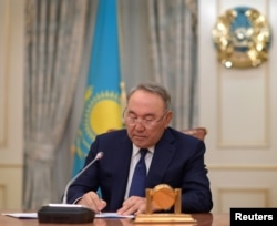 FILE - Kazakhstan's President Nursultan Nazarbayev writes during a televised address to announce his resignation, in Astana, Kazakhstan, March 19, 2019.