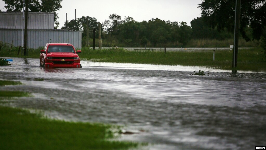 A car near Vermilion Bay is seen partially submerged in waters brought by Hurricane Laura approaching Abbeville, Louisiana, U.S., August 26, 2020. REUTERS/Kathleen Flynn REFILE