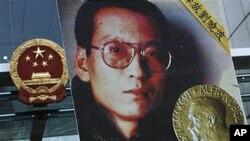ຜູ້ປະທ້ວງຄົນນຶ່ງ ຖືຮູບນາຍ Liu Xiaobo ນັກຄ້ດຄ້ານລັດຖະບານຈີນ ທີ່ຖືກຄຸກຢູ່ໃນເວລານີ້ ໃນລະຫວ່າງ ການໂຮມຊຸມນຸມປະທ້ວງ ຮຽກຮ້ອງໃຫ້ປ່ອຍຜູ້ກ່ຽວ ຢູ່ຕໍ່ໜ້າຫ້ອງການປະສານງານຂອງຈີນ ທີ່ຮົງກົງ (11 ຕຸລາ 2010)