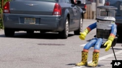 FILE- A car drives by HitchBOT, a hitchhiking robot in Marblehead, Massachusetts, July 17, 2015.