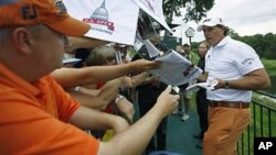 FILE - Phil Mickelson signs autographs at the U.S. Open golf tournament in Bethesda, Maryland, June 14, 2011. Mickelson has been accused of gaining financially from information he received about a Texas-based food company.