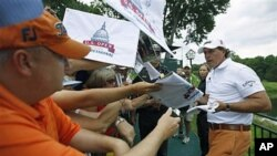 Phil Mickelson signs autographs after a practice round for the U.S. Open Championship golf tournament at Congressional Country Club in Bethesda, Maryland, June 14, 2011