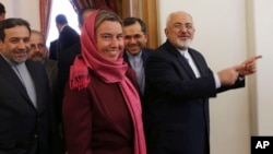 Iranian Foreign Minister Mohammad Javad Zarif, right, gestures while he makes way with European Union foreign policy chief Federica Mogherini, center, for a round of talks, in Tehran, Iran, July 28, 2015.