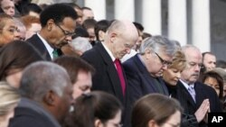Members of Congress and staff members observe a moment of silence for Rep. Gabrielle Giffords, D-Ariz., and other shooting victims, Monday, Jan. 10, 2011, on the East Steps of the Capitol in Washington