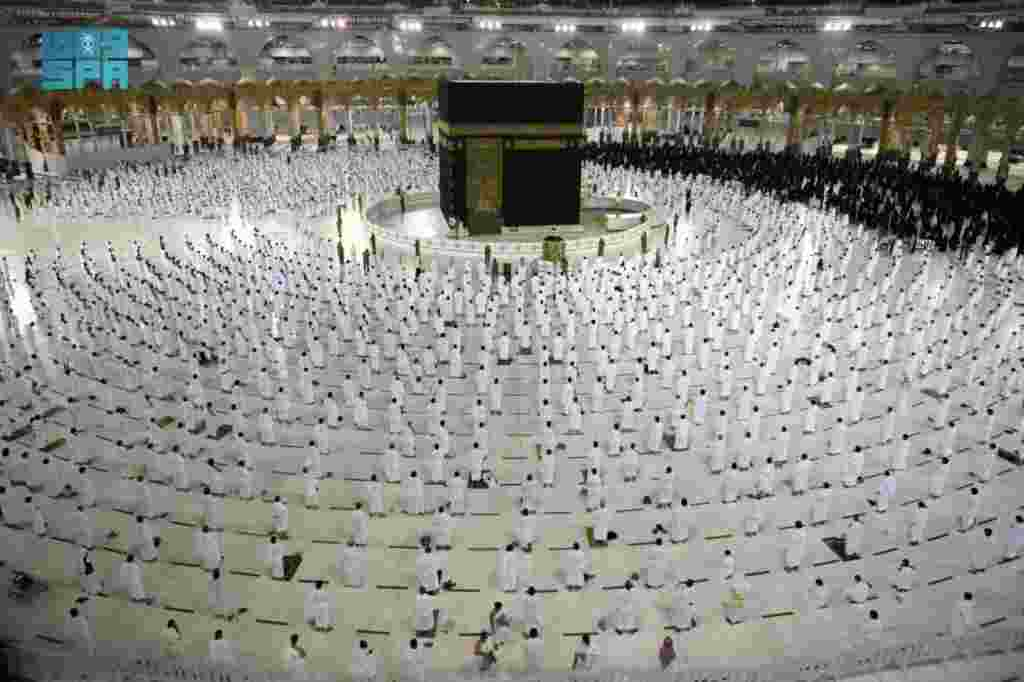 Muslims, maintaining social distancing, perform late night prayers on the night of 27th Ramadan in the Grand Mosque during the holy month of Ramadan, in the holy city of Mecca, Saudi Arabia. (Credit: Saudi Press Agency)