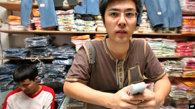 An unidentified Chinese trader stands near clothing materials for sale inside his shop at the China town trading building in Lagos, Nigeria. (file photo)