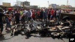 Cư dân vây quanh hiện trường vụ đánh bom xe tại một khu chợ ở thành phố Sadr, ngày 11/5/2016.