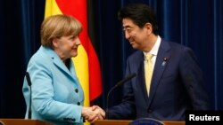 Germany's Chancellor Angela Merkel (L) shakes hands with Japan's Prime Minister Shinzo Abe