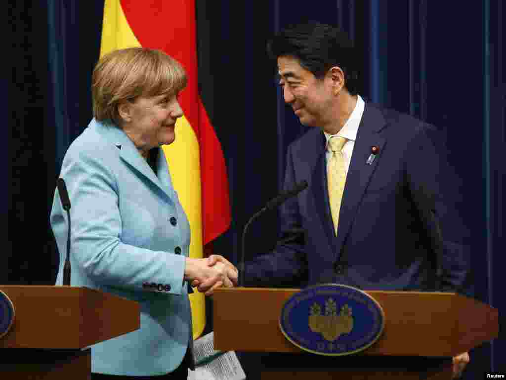 Germany's Chancellor Angela Merkel shakes hands with Japan's Prime Minister Shinzo Abe ​at the end of their joint news conference, in Tokyo, March 9, 2015.