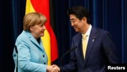 Kanselir Jerman Angela Merkel (kiri) berjabat tangan dengan PM Jepang Shinzo Abe seusai konferensi pers di Tokyo (9/3).