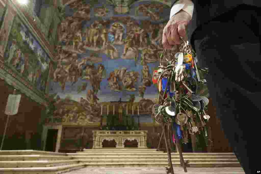 """Gianni Crea, the Vatican Museums chief """"Clavigero"""" keys keeper, walks through the Sistine Chapel as he prepares to open the museum, at the Vatican."""