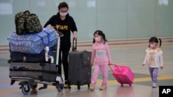 Passengers wear face masks after arriving at Hong Kong airport, Monday, March 23, 2020. Hong Kong will close its border to non-residents for 14 days starting from Wednesday, its chief executive announced on Monday after the number of coronavirus patients