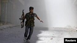 Binh sĩ của Quân đội Giải phóng Syria bỏ chạy tránh đạn pháo kích của quân đội chính phủ Syria vào khu phố Salah al-Din ở trung tâm Aleppo, ngày 5/8/2012