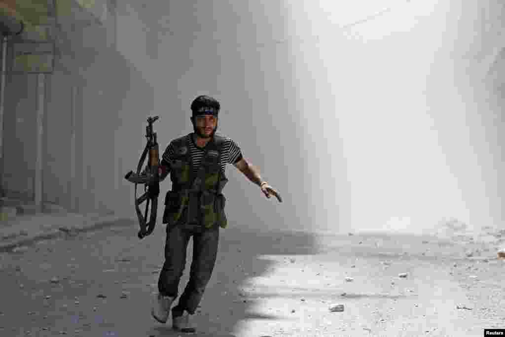 8月5日,在阿勒颇城的萨拉赫丁区战火中,一名反政府的叙利亚自由军躲避政府军的坦克炮 弹射击