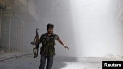 8月5日,在阿勒颇的萨拉赫丁区,一名叙利亚哟唷军的战斗在躲避政府军坦克的轰击