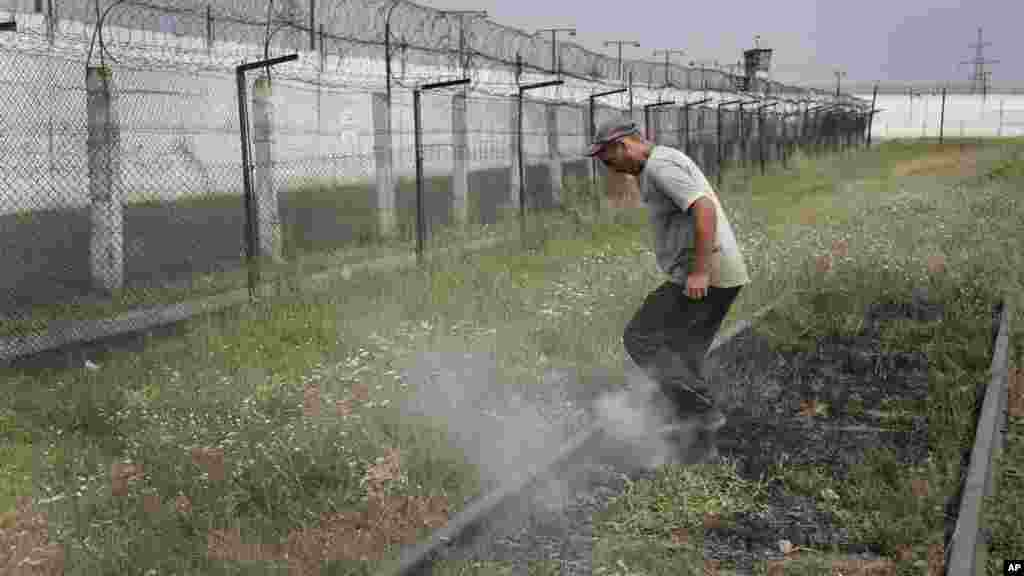 A prisoner tramples smoldering grass in a high-security facility after shelling in Donetsk, eastern Ukraine, Aug. 11, 2014.