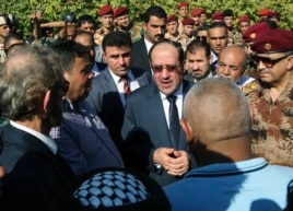 Iraq's Prime Minister Nouri al-Maliki, center, attends the funeral ceremony of Major General Negm Abdullah Ali, commander of the army's sixth division, at the Defense Ministry in Baghdad, July 7, 2014.