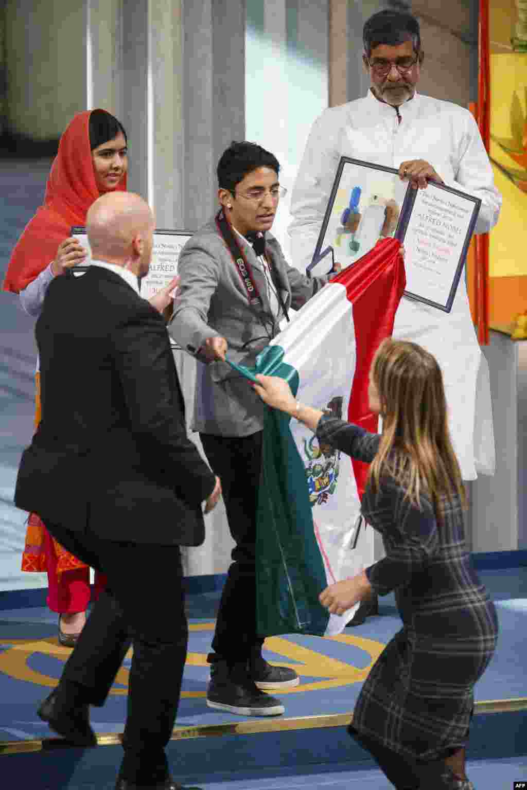 Nobel Peace Prize laureates Malala Yousafzai (left) and Kailash Satyarthi look on as security officers lead away a man displaying a flag of Mexico during the Nobel Peace Prize awards ceremony at the City Hall in Oslo, Norway.