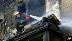 17일 우크라이나 동부 도네츠크에서 발생한 교전으로 불이 난 가운데, 소방관이 화재를 진압하고 있다.