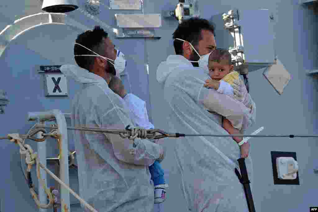 "Rescuers holds babies as the Italian military ship ""Chimera"" with around 350 would be immigrants onboard, arrives in the port of Pozzallo, Sicily, one day after a rescue operation off the coast of Sicily."