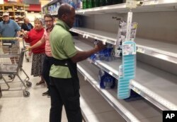 Un empleado de la cadena de supermercados Publix vuelve a llenar con botellas de agua los estantes vacíos en Surfside, Florida. Septiembre 6, 2017.
