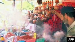 A man spreads incense smoke over the goods to ward off the evil eye, in the marketplace in Cairo, July 2011