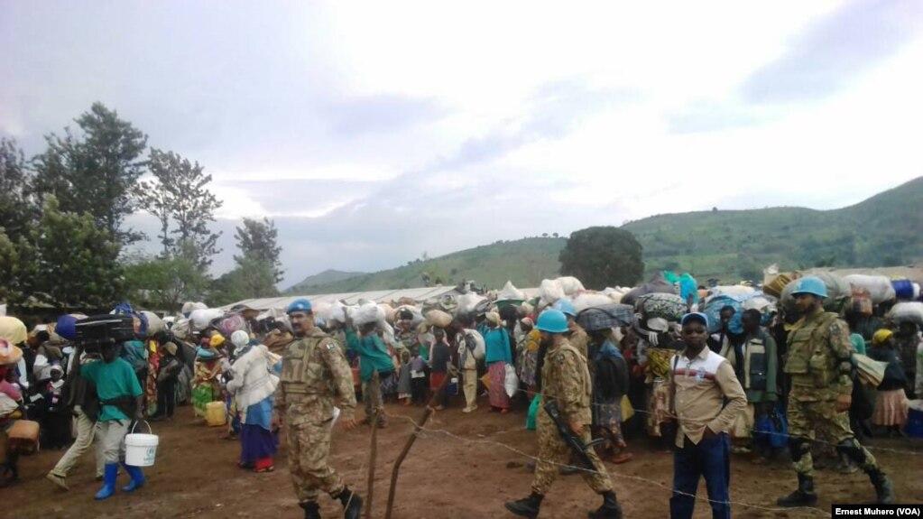 Les réfugiés en train de quitter le camp de Kamanyola encadrés par les éléments de la Mission de l'ONU, en direction du Rwanda, Kamanyola, Sud-Kivu, RDC, 7 mars 2018. (VOA/Ernest Muhero)