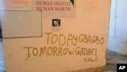 With a nod to events in Ivory Coast, graffiti reflects Libyan rebel demands that leader Moammar Gadhafi leave, April 12, 2011