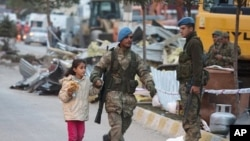 A soldier helps a girl to cross a street after an earthquake in Ercis, Turkey October 24, 2011.