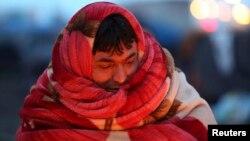 Một người di dân Afghanistan quấn chăn quanh người để giữ ấm trước khi bị cảnh sát Pháp sơ tán khỏi một trại được dựng tạm ở Calais, miền bắc Pháp.