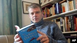 "FILE - Mark Haddon, author of ""The Curious Incident of the Dog in the Night-Time,"" poses with a copy of his novel, Oxford, England, March 2004."