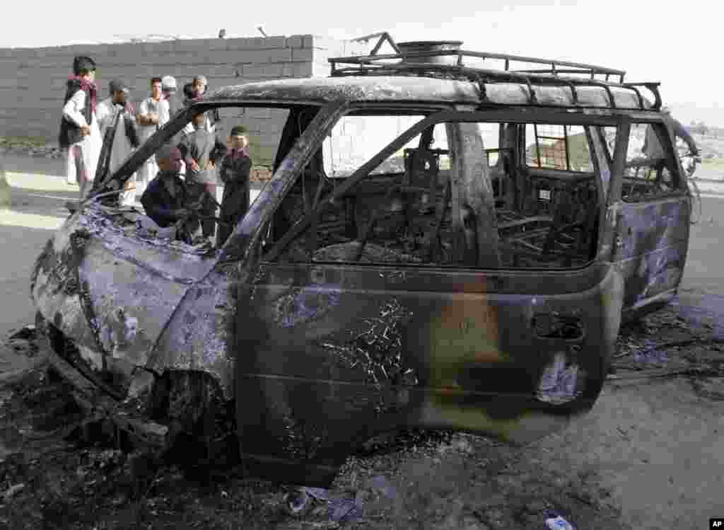 Men investigate the remains of a burnt vehicle after a suicide attack in Ghazni Province, Afghanistan, August 29, 2013.