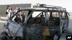 Warga setempat memeriksa kendaraan yang terbakar pasca serangan bunuh diri di provinsi Ghazni, Afghanistan (29/8).