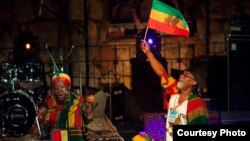 Vivien Jones stands behind the drummers waving the Jamaican flag at the Jerusalem Sacred Music Festival. (Courtesy Hanan Bar Assulin/Jerusalem Season of Culture)