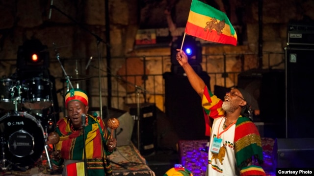 Vivien Jones stands behind the drummers waving the Jamaican flag at the Jerusalem Sacred Music Festival. (Courtesy Hanan Bar Assulin/Jerusalem Season of Culture)