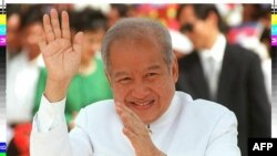 FILE - Cambodian King Norodom Sihanouk waving to bystanders on his way to greeting Indonesian President Suharto in Phnom Penh.