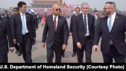Homeland Security Secretary Jeh Johnson, in sunglasses, gets briefed while walking through Tiananmen Square in Beijing, China, April 10, 2015.
