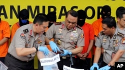 Indonesian Deputy National Police Chief Muhammad Syafruddin, center, checks huge quantities of suspect confiscated alcohol during a press conference in Jakarta, Indonesia, Wednesday, April 11, 2018.