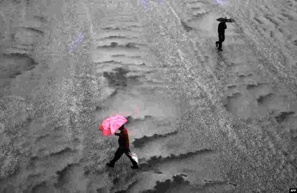 Pedestrians walk during a heavy hailstorm in the northern hill town of Shimla, India.