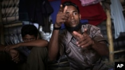 In this Nov. 24, 2017, photo, Li Juhar, who fled to Bangladesh from Myanmar's Rakhine State, becomes animated, forming both his hands into the shape of guns, when he speaks of soldiers flooding into his village.