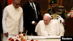 Bangladesh's President Abdul Hamid watches as Pope Francis writes in a book at the presidential palace in Dhaka, Bangladesh, Nov. 30, 2017.