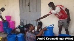 Nétoua Ernestine le Néribar entourée de quelques bénévole au service de la population vulnérable, au Tchad, le 2 avril 2020. (VOA/André Kodmadjingar).